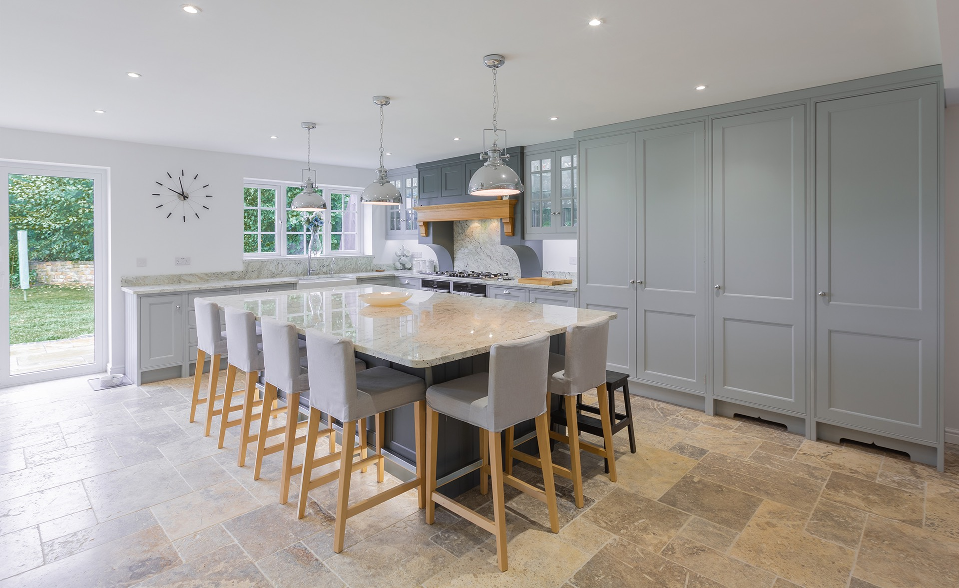 Modern hand built kitchen with wooden cupboards, granite island and chairs with tiled flooring