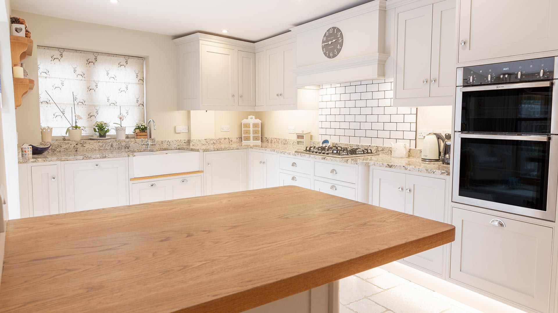 White designed kitchen with wooden island